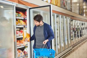 Customer in the supermarket is standing at frozen food in the refrigerator shelf and looks at a pack of French fries