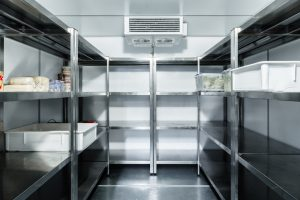 Refrigerator chamber with steel shelves in a restaurant close up