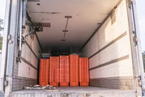 Fishing and seafood logistics industry - plastic fish crates inside refrigerated chilled truck in New Zealand, NZ