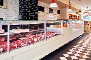 Variety of raw fresh veal meat in the refrigerated display of a butcher shop