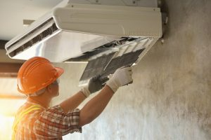 A young Asian air conditioner technician or air-conditioning installation technician is about to repair air conditioning in homes and buildings.Air conditioner repairmen work on home unit.